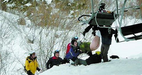 Man hanging naked from ski-lift